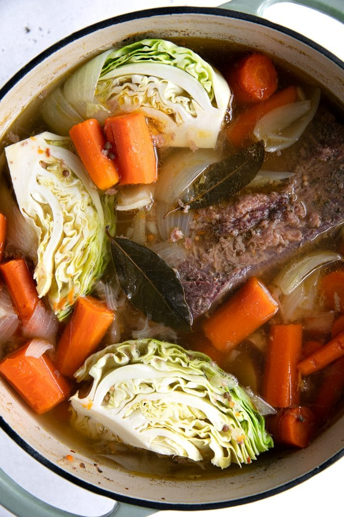 Large Dutch oven filled with cooking corned beef, cabbage, carrots, and onions.