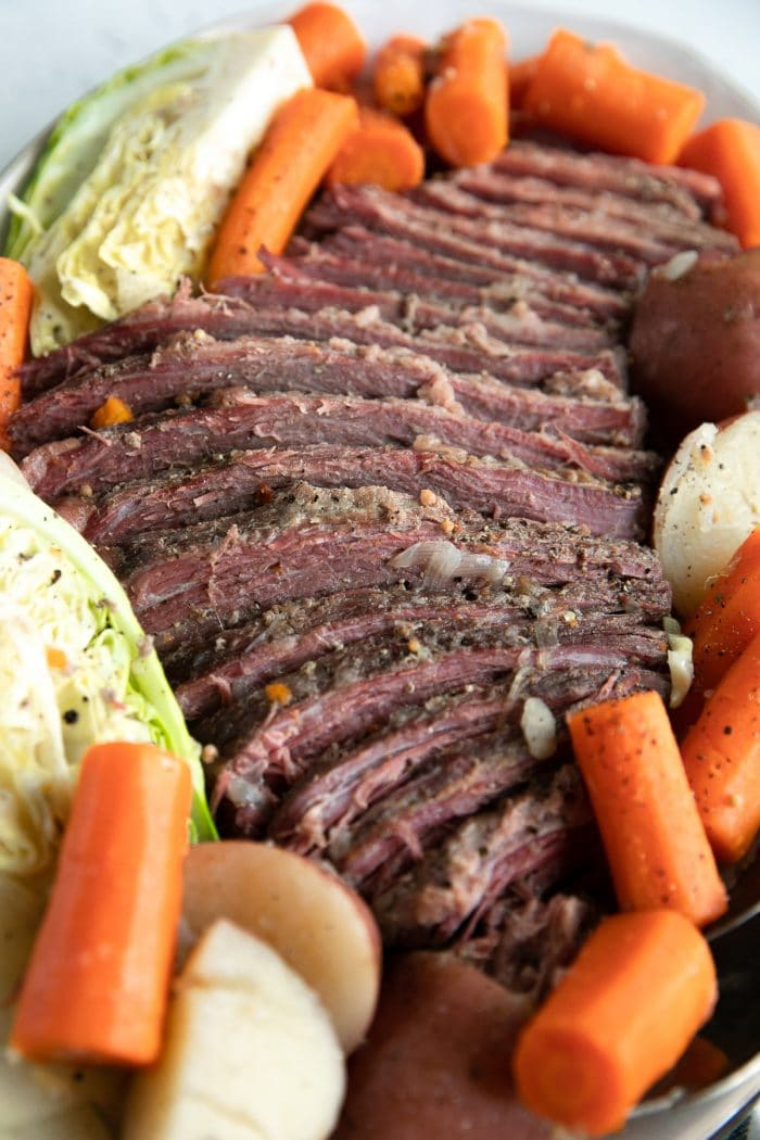 Large cooked and sliced corned beef brisket served on a large platter with carrots, potatoes, and cabbage.