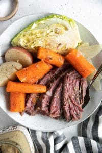 Dinner plate filled with slices of corned beef, carrots, potatoes, and cabbage wedges.