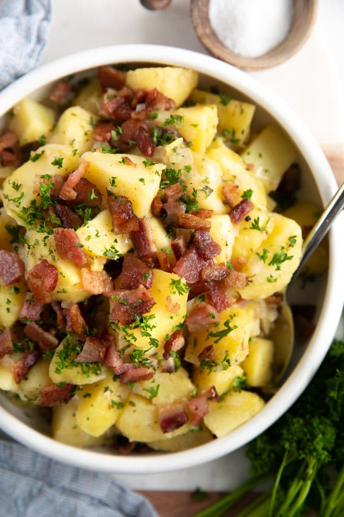 Overhead image of a large white serving bowl filled with German potato salad garnished with bacon and minced parsley.