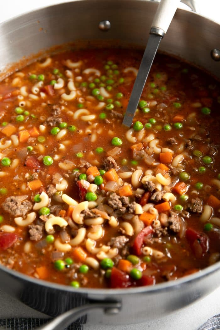 Large pot filled with Hamburger Soup made with ground beef, tomatoes, macaroni noodles, peas, and carrots.