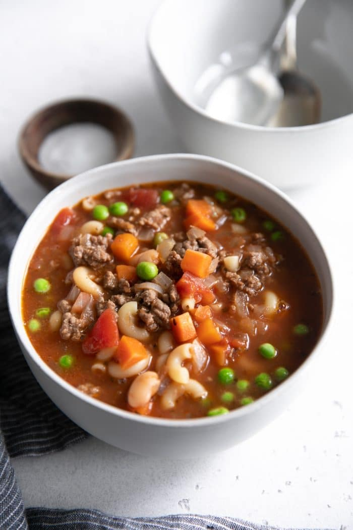 White serving bowl filled with filled with Hamburger Soup made with ground beef, tomatoes, macaroni noodles, peas, and carrots.