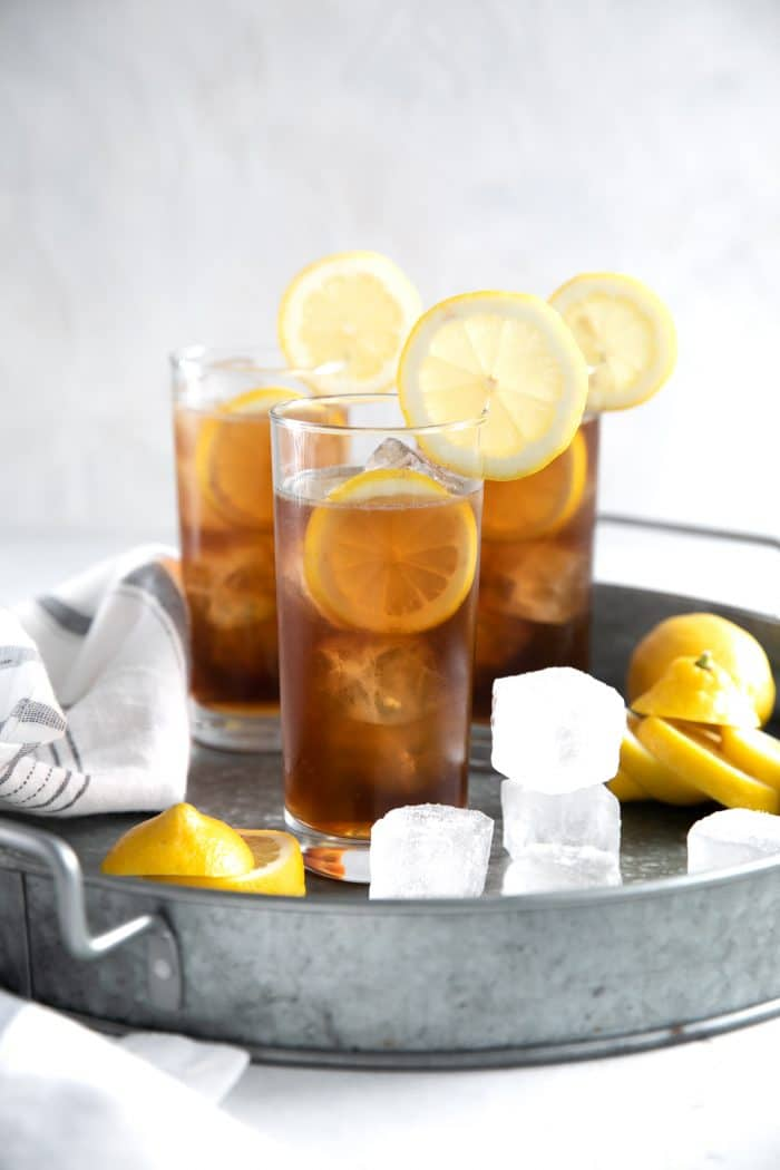 Three ice-cold Long Island Iced Tea on a large metal serving tray.