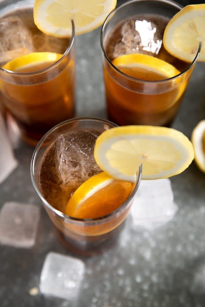 Three Long Island Iced Teas garnished with fresh lemon.
