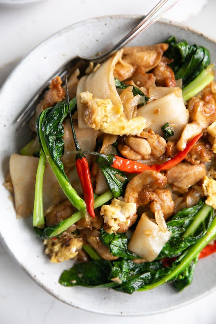 A plate of pad see ew (Phat si-io) made with chicken and chinese broccoli and garnished with Thai red chilis.