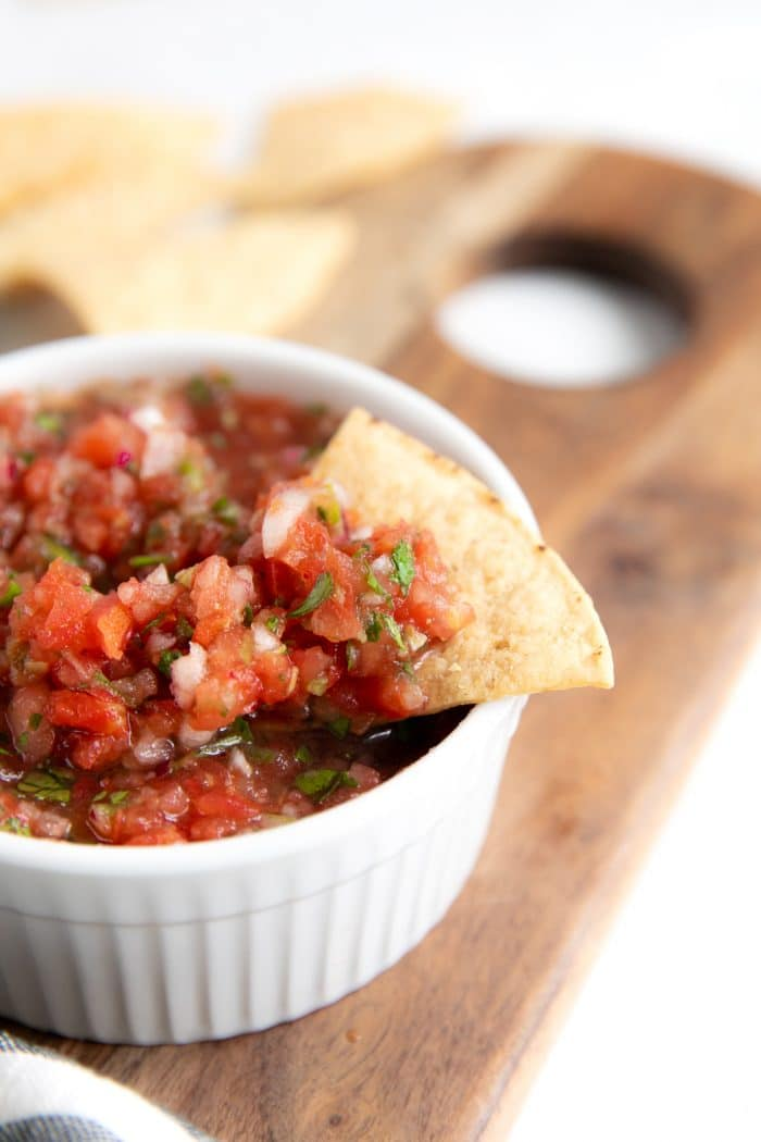 Homemade salsa in a small white bowl served with tortilla chips.