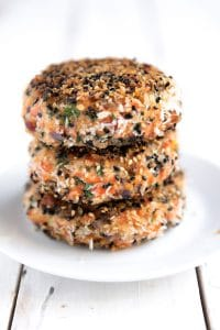 Three fully cooked salmon burger patties crusted with black and white sesame seeds.