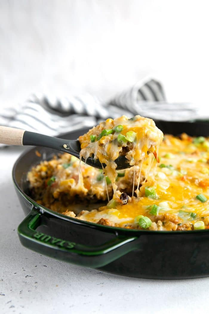 A pan of Quinoa Casserole with melting cheese being lifted