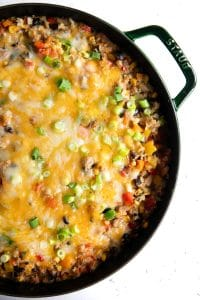 Large cast iron skillet filled with cheesy baked quinoa mixed with fresh veggies, black beans, corn, and ground chicken.