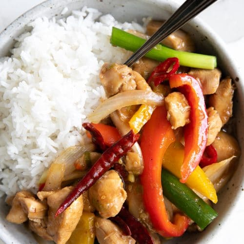Szechuan chicken with colored bell peppers served with white rice in a white bowl.