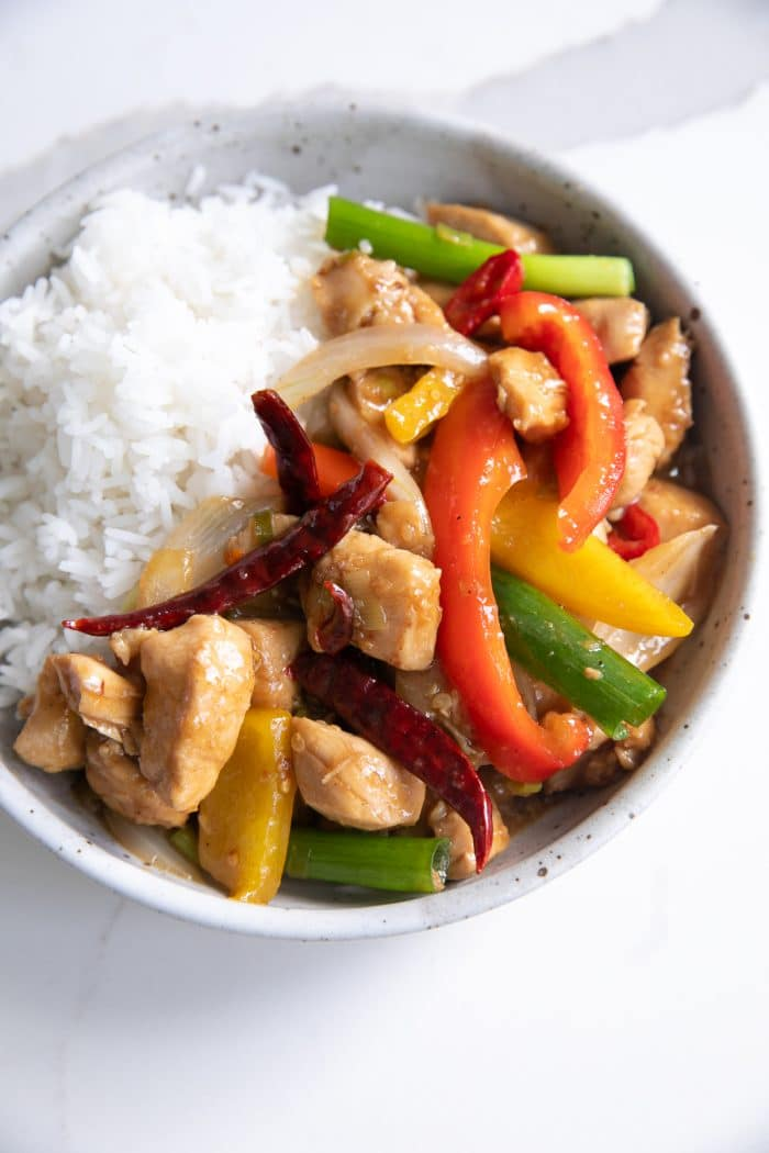 A bowl of Kung Pao chicken with rice