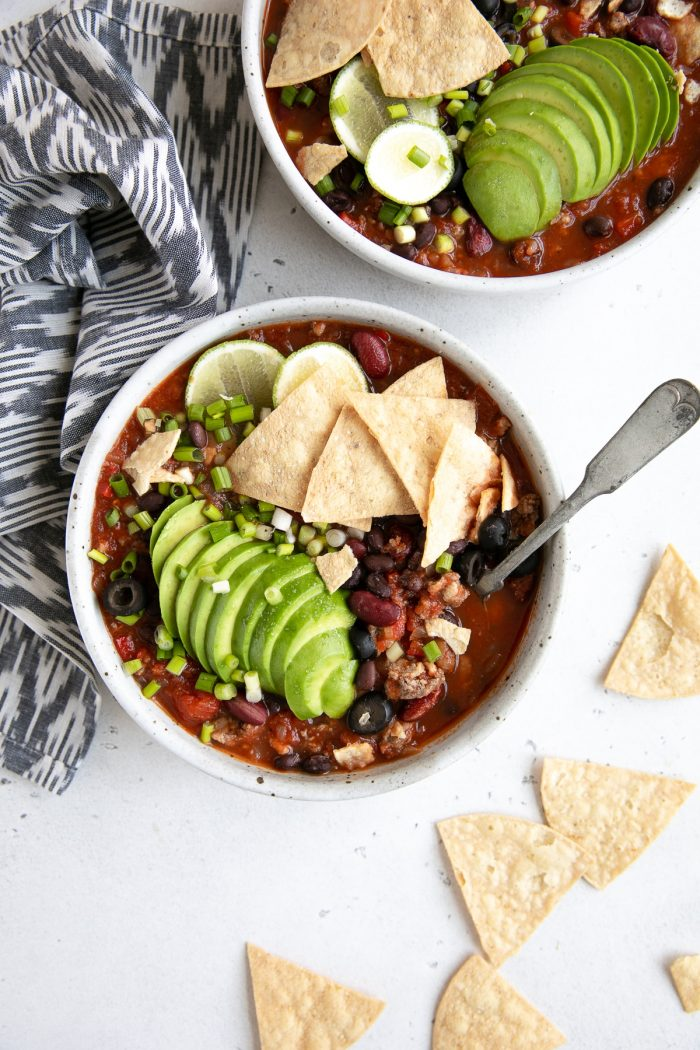 Taco soup garnished with avocado and tortilla chips.
