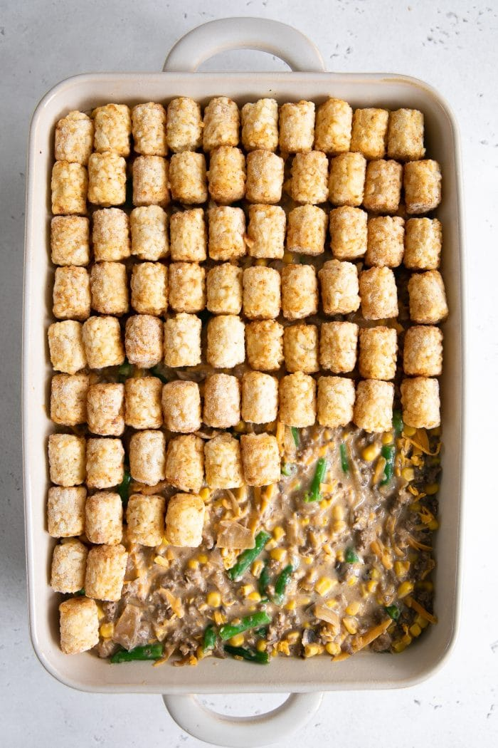 Placing frozen tater tots on top of the tater tot casserole meat mixture.