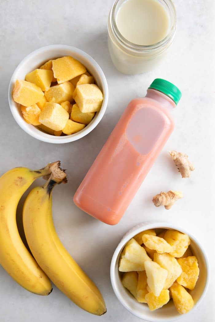 Ingredients needed to make a carrot smoothie including frozen mango, pineapple, banana, carrot juice, ginger, and oat milk.