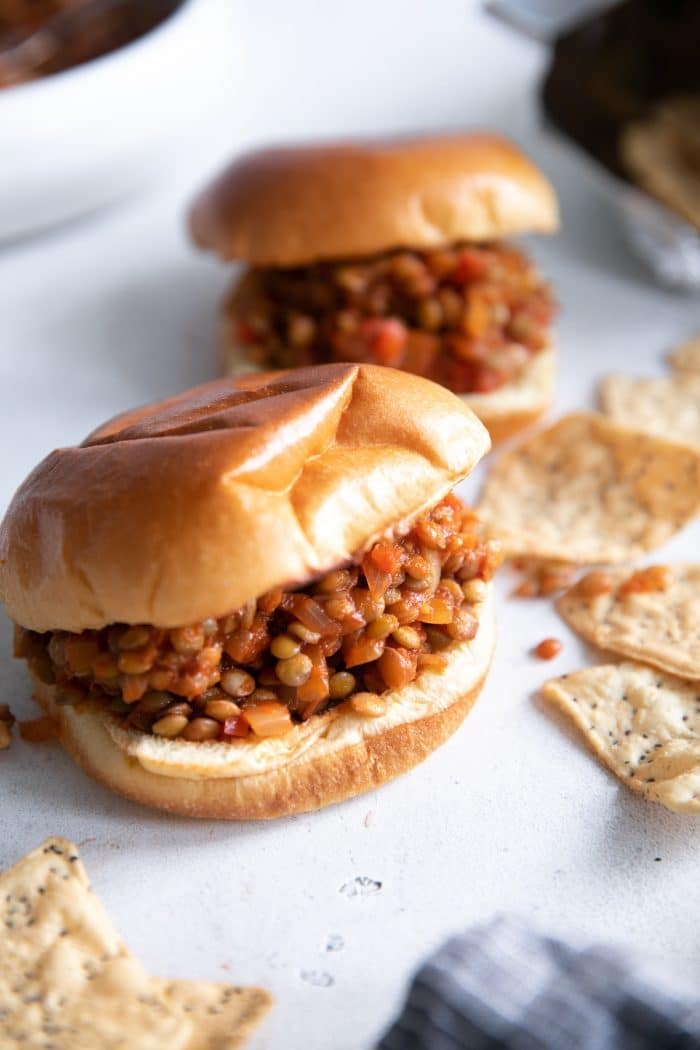 Two vegetarian sloppy joes served on a brioche bun with a side of chips.