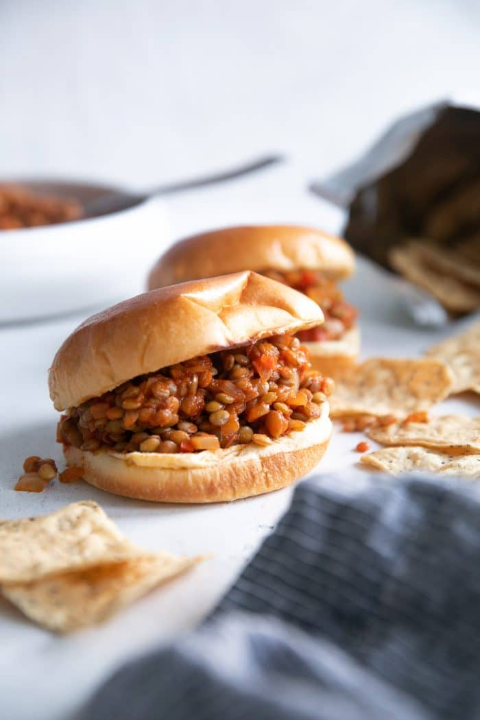 Two lentil sloppy joes served on a brioche bun with a side of chips.