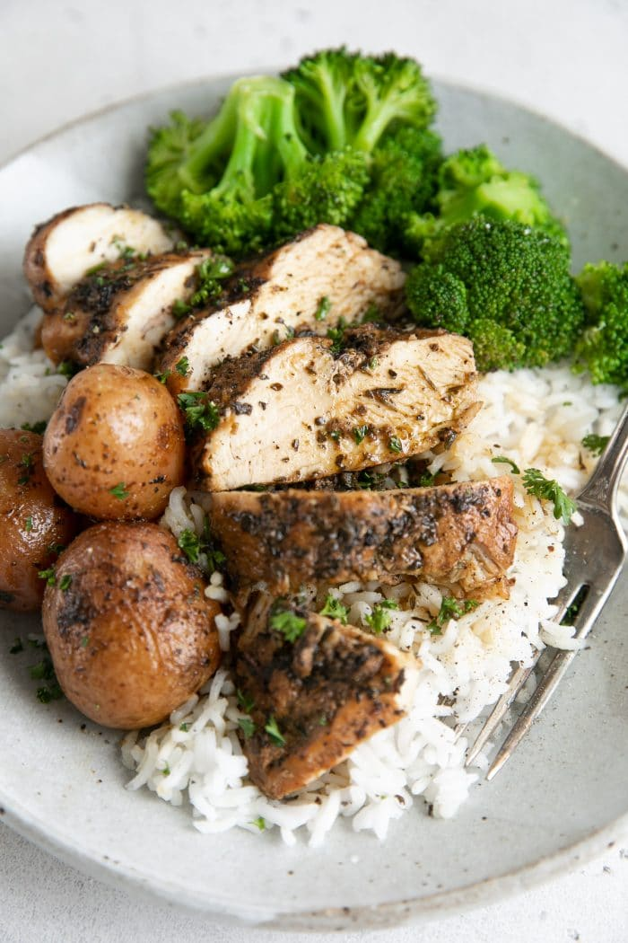 Sliced chicken breast and potatoes served over rice with cooked broccoli.