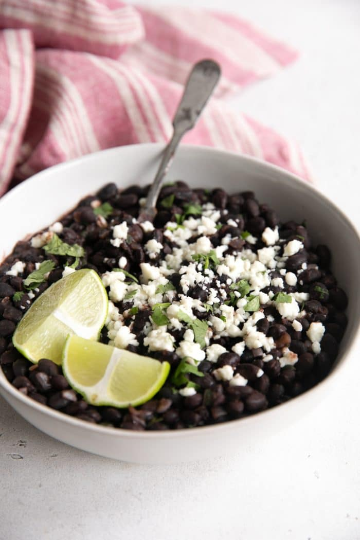 White bowl filled with Mexican-style black beans garnished with cotija cheese and fresh cilantro.