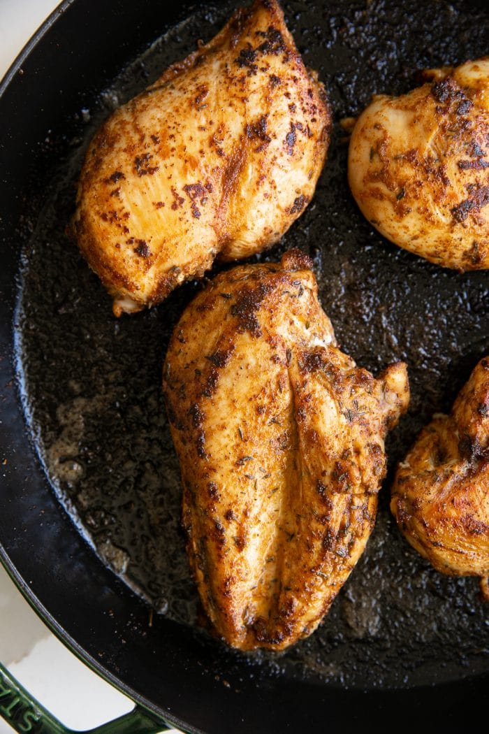 Searing blackened chicken breasts in a large skillet.