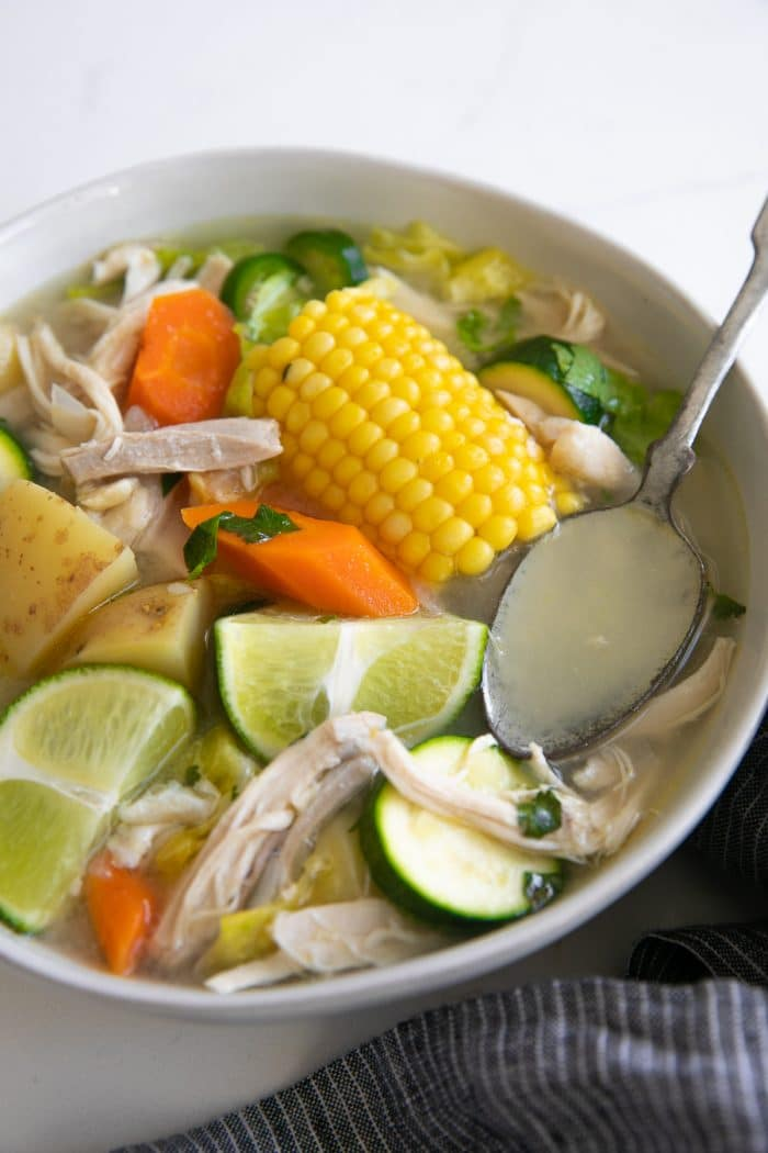 Large white shallow bowl filled with caldo de pollo made with chicken, carrots, corn, lime juice, potatoes, and zucchini.