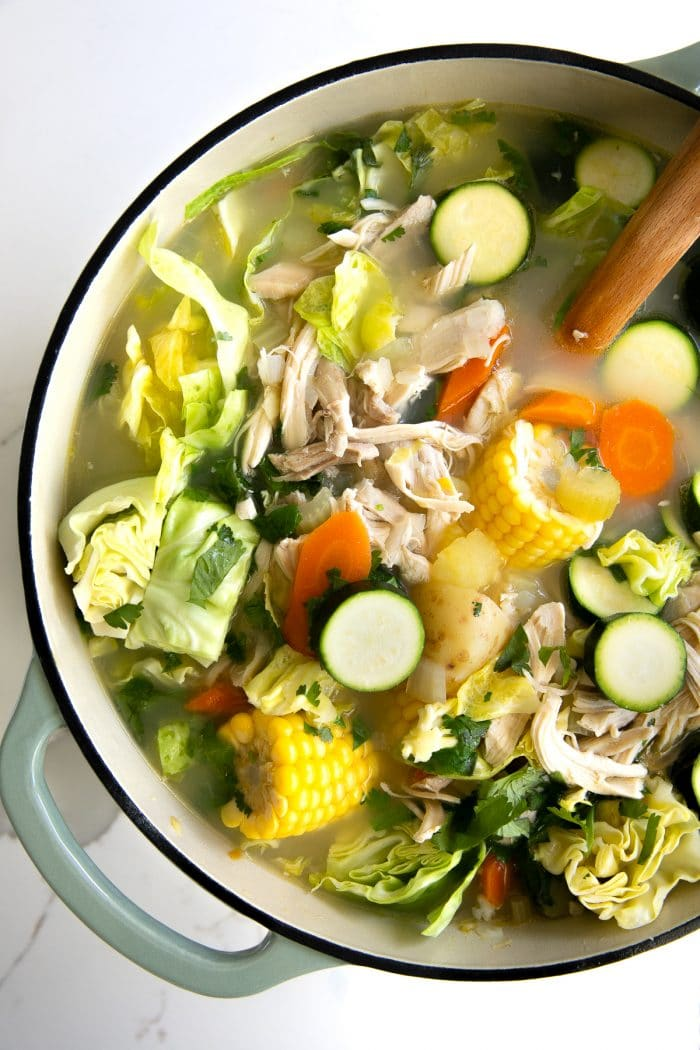 Large pot of soup filled with a clear chicken broth, zucchini, carrots, corn, shredded chicken, cabbage and potatoes.