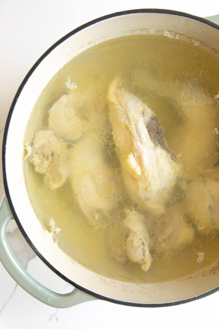 Boiling chicken pieces in a large pot.
