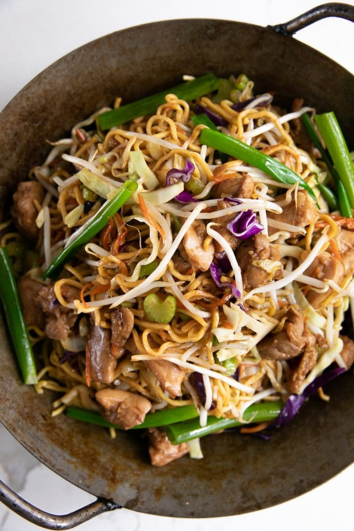 Stir fried noodles is a large wok.