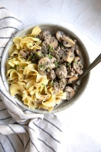 Large white serving dish filled with egg noodles and hamburger stroganoff garnished with fresh parsley.