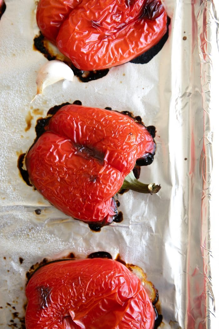 Halved roasted red peppers on a large baking sheet.