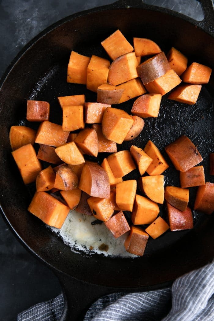 Cubes of sweet potato cooking in a large cast iron skillet.