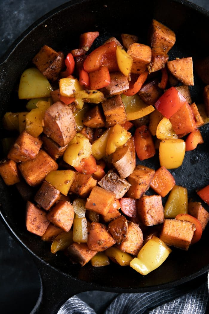 Sweet potatoes and bell peppers covered in cajun spices cooking in a cast iron skillet.