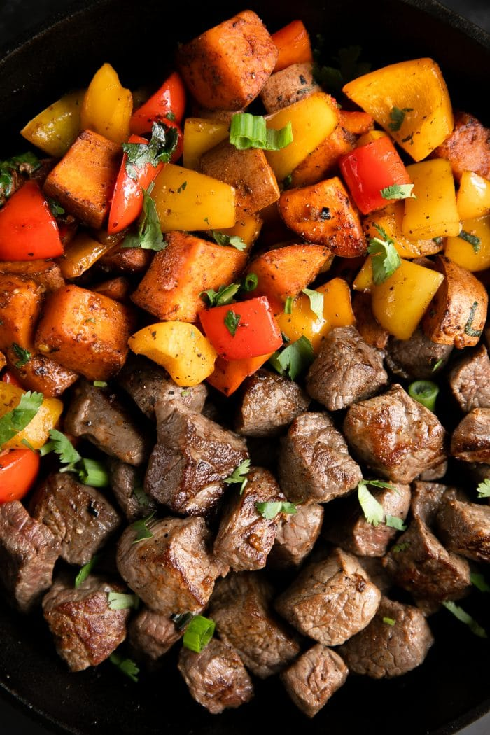 Large cast iron skillet filled with cooked steak bites and cajun spiced sweet potatoes and peppers.