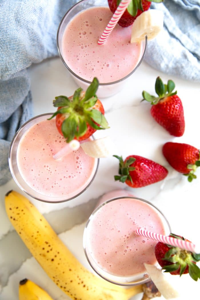 Overhead image of three glasses filled with strawberry banana smoothie.