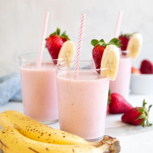 Three glasses with strawberry banana smoothie garnished with one strawberry and one banana slice.