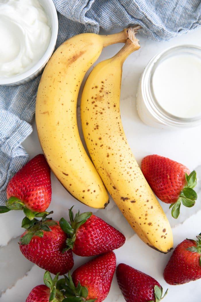Ingredients for banana strawberry smoothie including bananas, strawberries, milk, and yogurt.