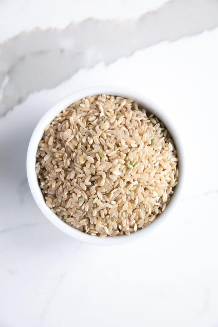 Uncooked short-grain brown rice in a small white bowl.