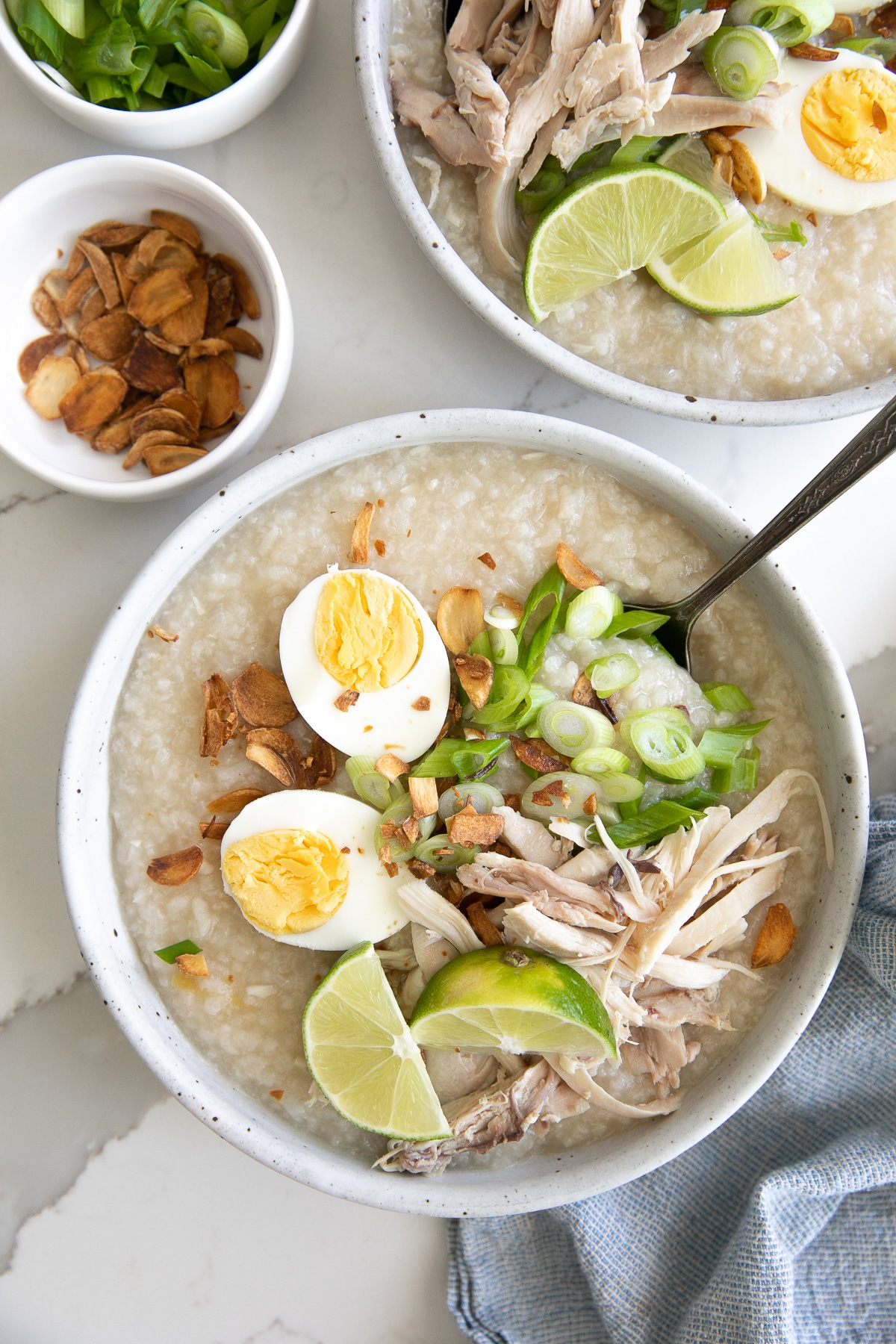 Bowls filled with cooked arroz caldo and garnished with fried garlic, scallions, hard-boiled egg, and shredded chicken.