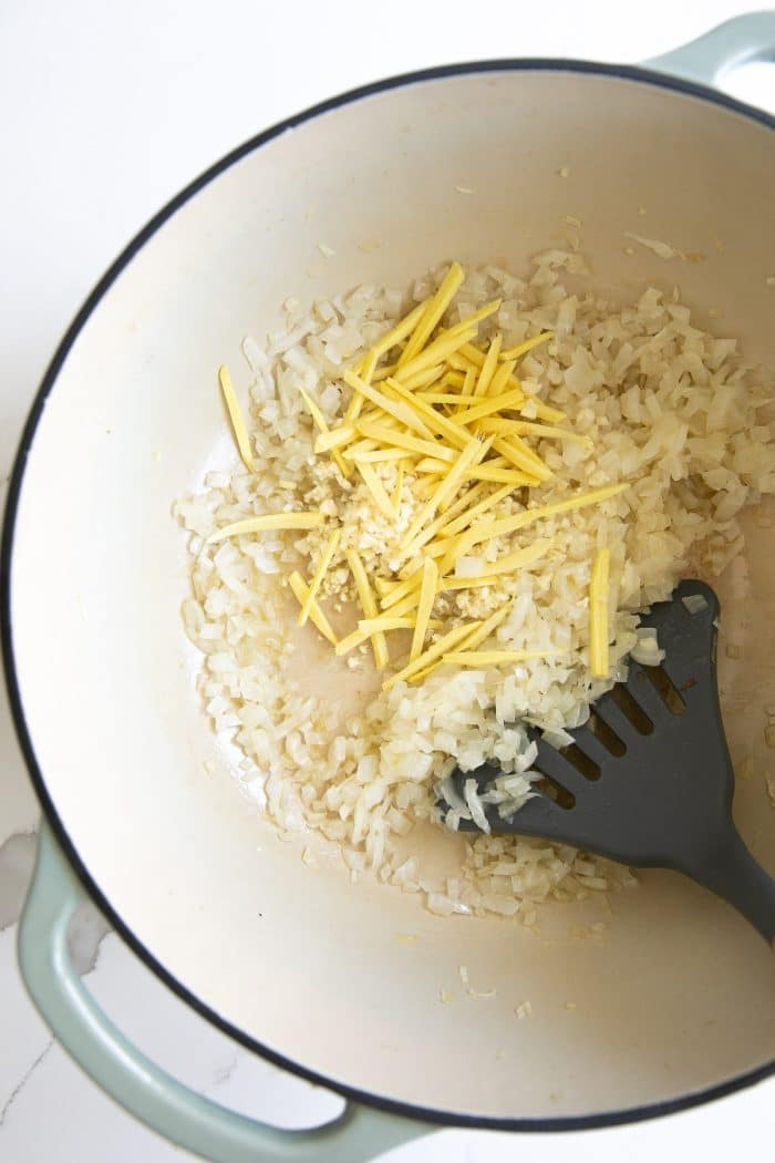 Toasting rice in a large pot with oil, garlic, and julienned ginger.