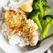 Juicy baked lemon chicken breast served on top of white rice with a side of cooked broccoli.