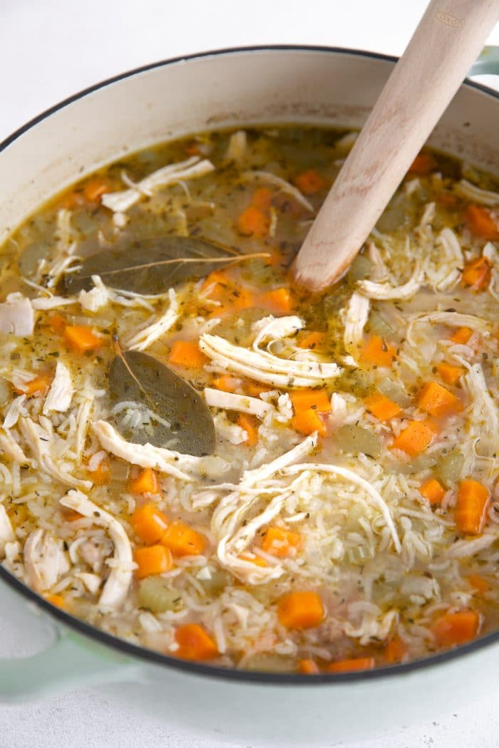 Large pot filled with chicken and rice soup loaded with carrots and celery.
