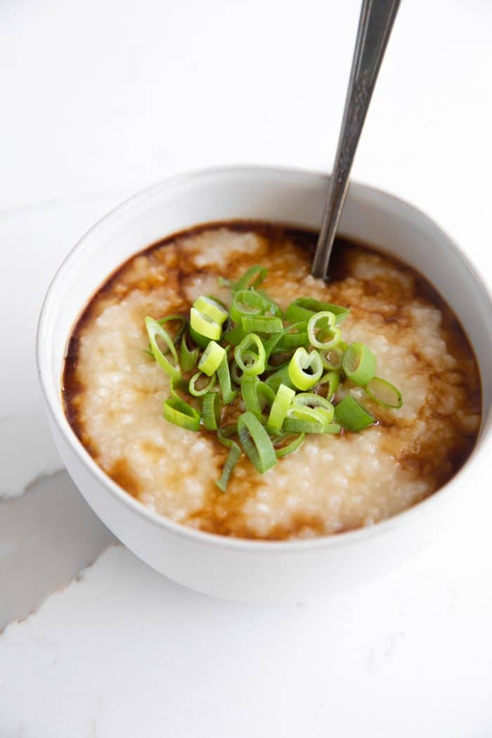 Simple homemade congee in a small white serving bowl topped with green onions and garnished and drizzled with sesame oil and soy sauce.