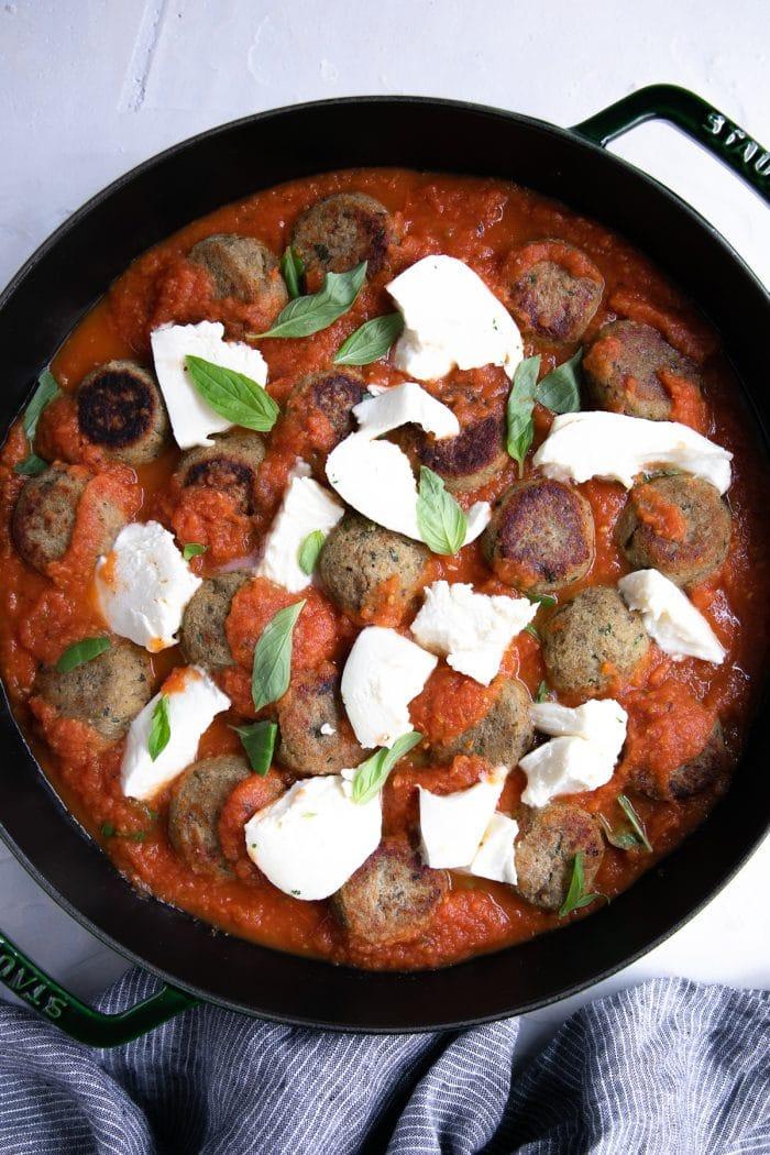 Homemade eggplant meatballs with fresh tomato sauce and basil.