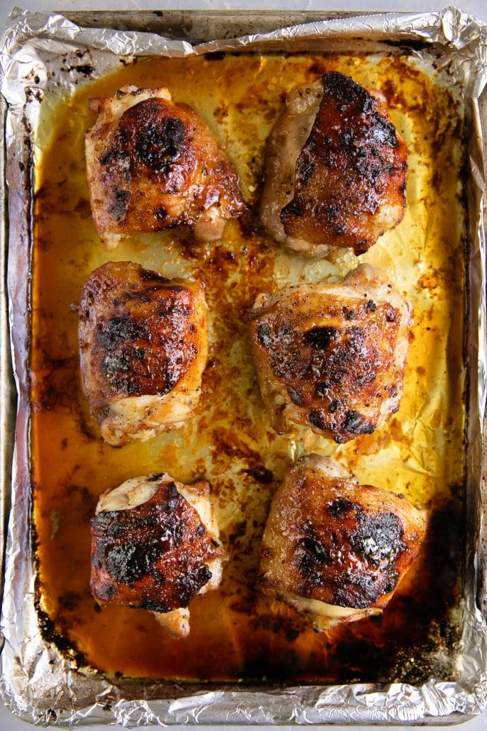 Large rimmed baking sheet with six cooked bone-in skin-on chicken thighs with honey soy marinade.