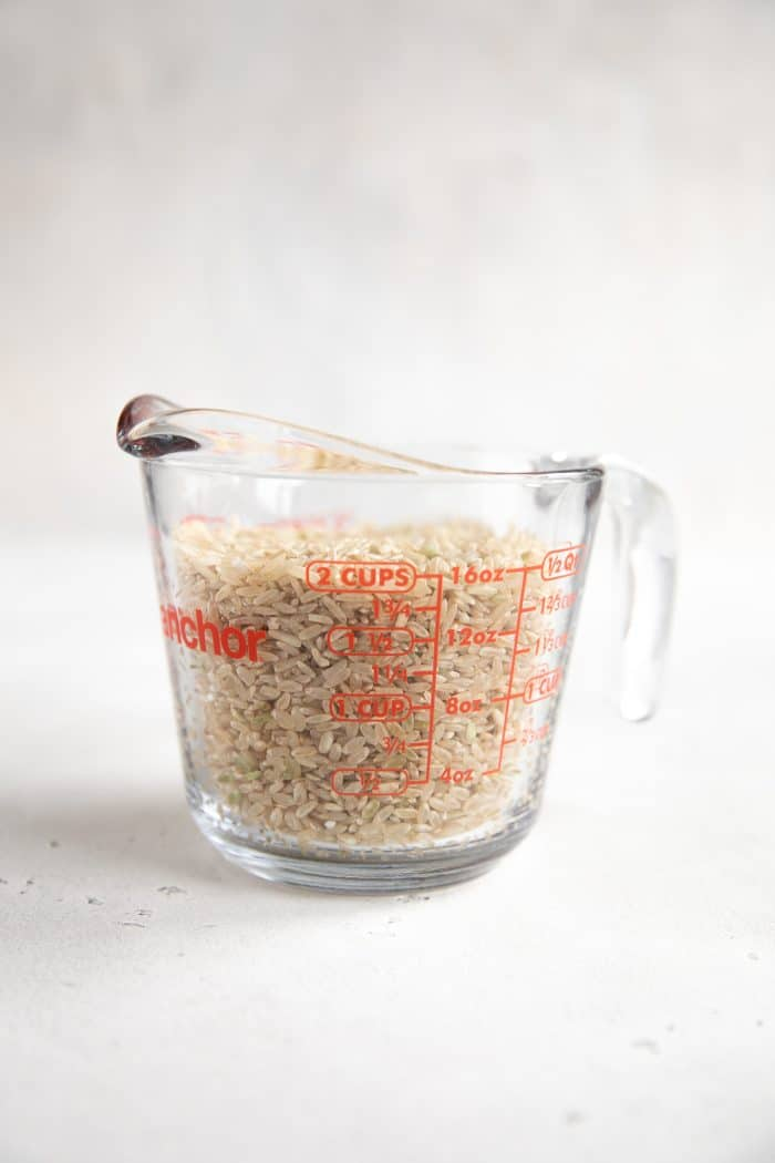 Glass measuring cup filled with long-grainbrown rice.