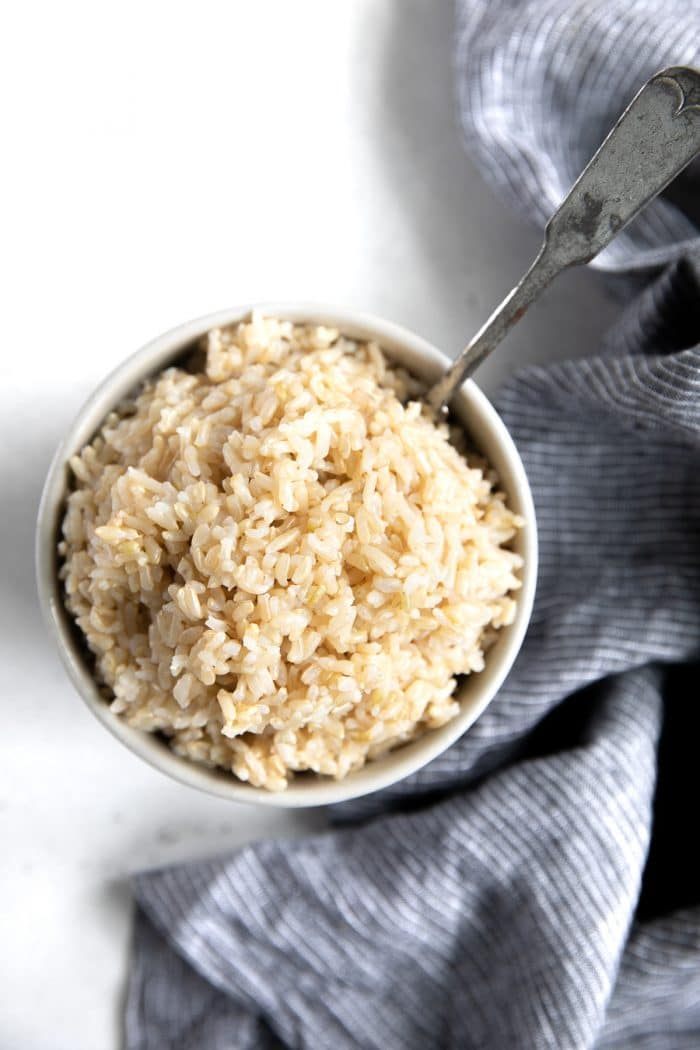 Small white bowl filled with soft and fluffy cooked brown rice.