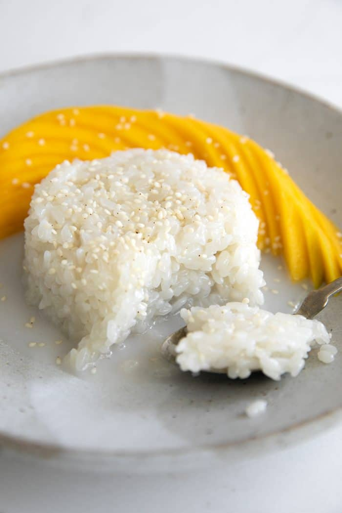 Small serving of mango sticky rice topped with coconut cream and sesame seeds and served with sliced mango.