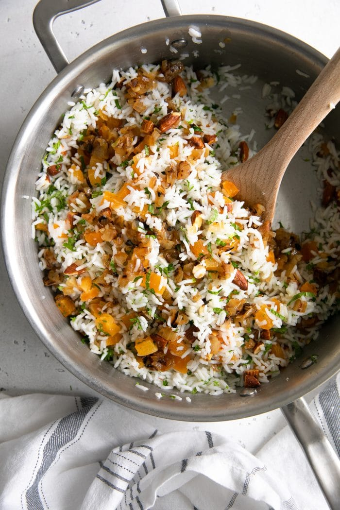 Overhead image of a large saute pan filled with cooked basmati rice mixed with caramelized onions, herbs, almonds, dried apricots, and lemon juice.