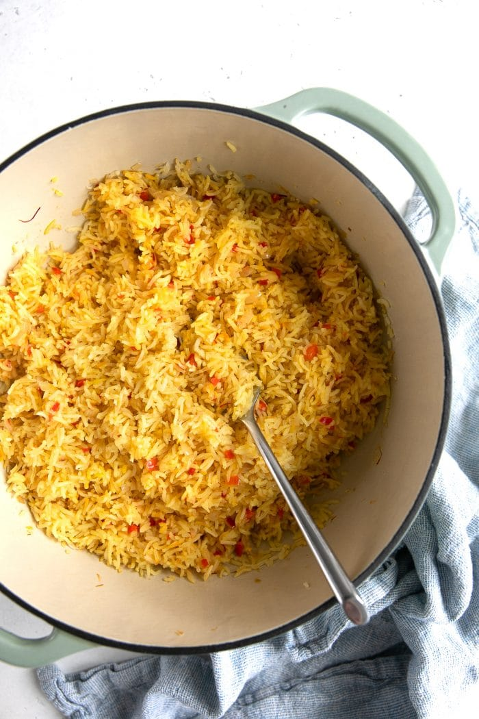 Fork fluffing a large pot of yellow-colored spanish rice.