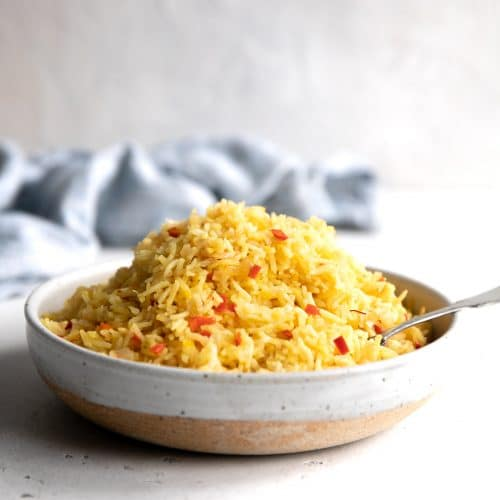 Bowl filled with yellow cooked rice dotted with small pieces of red bell peppers.