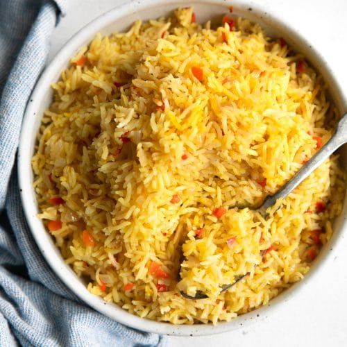 Overhead view of a large bowl filled with yellow, fluffy Spanish rice.
